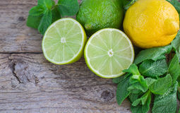 Lime, lemon and mint. Juicy ripe citrus on an old wooden table - lime, lemon and mint Stock Image