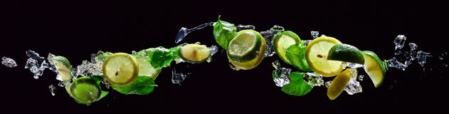 Lime and lemon pieces with peppermint. Lime and lemon pieces with leaves of peppermint on black background stock photography