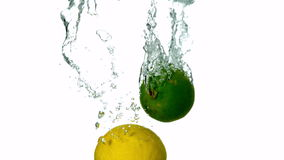 Lime and lemon plunging into water on white background