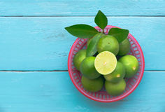 a Lime lemon in red bucket on blue wooden background. copy space royalty free stock photo