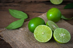 a Lime lemon with sack cloth on rustic wooden background. Stock Photo
