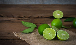 a Lime lemon with sack cloth on rustic wooden background. royalty free stock photography