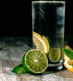 Lime and lemon splash with ice and some detox water. Food photo of fresh lime and lemons. This is perfect for background or magazines related to food and kitchen Royalty Free Stock Photos