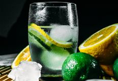 Lime and lemon splash with ice and some detox water. Food photo of fresh lime and lemons. This is perfect for background or magazines related to food and kitchen royalty free stock images