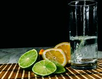 Lime and lemon splash with ice and some detox water. Food photo of fresh lime and lemons. This is perfect for background or magazines related to food and kitchen Royalty Free Stock Photography