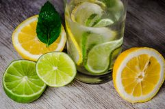 Lime and lemon splash with ice and some detox water. Food photo of fresh lime and lemons. This is perfect for background or magazines related to food and kitchen Royalty Free Stock Image