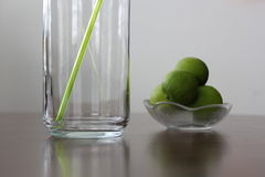 Lime lemon straw. Limes in small bowl and green straw in a tall glass Stock Images