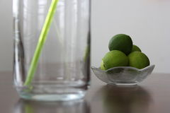 Lime lemon straw. Limes in a small transparent bowl and green twisted straw in a tall glass Stock Photography