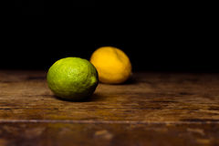 Lime and lemon on wooden surface Royalty Free Stock Photos