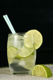Lime and lemonade. Frosted glass of lime and lemonade with ice and lime slices on black background Royalty Free Stock Photo