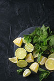 Lime and lemons with mint. Sliced Lime and lemons with bunch of fresh mint on black slate stone board over black textured background. Top view Royalty Free Stock Photos