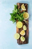 Lime and lemons with mint. Sliced Lime and lemons with bunch of fresh mint on wooden cutting board over light blue textured background. Top view. With copy space Stock Images