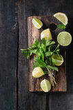 Lime and lemons with mint. Sliced Lime and lemons with bunch of fresh mint on wooden cutting board over old wood background. Top view Stock Images