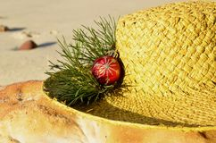 Christmas on Sunny beach, red glitter Christmas decoration on a light green straw hat resting on an orange rock, Christmas in July Royalty Free Stock Photos