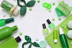 Lime mint composition of beauty threatment products in green colors on a white concrete background: shampoo, soap, bath salt, towe Stock Photo