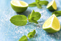 Lime and mint leaves. Lime and mint leaves on a blue wooden background Royalty Free Stock Photography