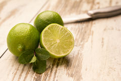 Lime and mint are on a light wooden table. One lime is cut. Nearby is a knife Royalty Free Stock Image
