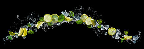 Lime and mint with water splash. Lime and lemon pieces with mint and ice in water splash stock images