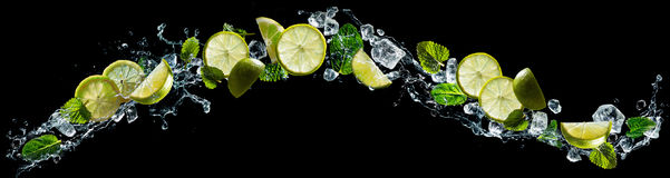Lime and mint with water splash. Lime and lemon pieces with mint and ice in water splash Stock Photo