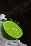 Lime and mint with white cloth on slate background Stock Photos