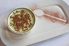 Lime Mousse. A ramekin of lime mousse with a chocolate dusted spoon Royalty Free Stock Image