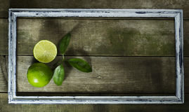 Lime in the old frame. On a wooden background stock images