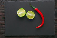 Lime and pepper  on stone board Stock Photos