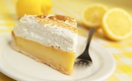 Lime pie. Fresh and delicious lime pie with fork and lemon in background Royalty Free Stock Image