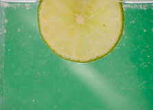 Lime. Piece of lime in the water with green background Stock Photography