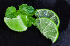 Lime pieces and mint on a slate background Royalty Free Stock Photography