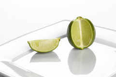 Lime on a plate. A single lime on a porcellain plate Royalty Free Stock Photo