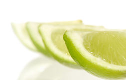 Lime quarters. And their reflections in glass surface Stock Image