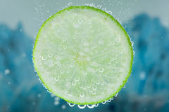 Lime refresher concept. Close-up of lime green slice on blue background diving inside carbonated water with bubbles Royalty Free Stock Images