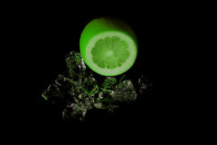 Lime on the rocks. Lime with ice on a black background Royalty Free Stock Image