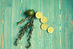Lime and rosemary on wooden table Royalty Free Stock Photo