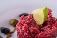Lime on single portion of tartar steak Stock Images