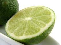 Lime slice. Lime on white plate close-up on white Stock Image