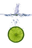 Lime slice falling into the water. On white background Royalty Free Stock Images