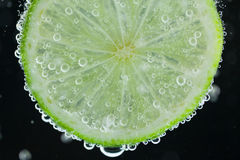 Lime slice falling into water Royalty Free Stock Photos