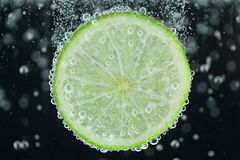 Lime slice falling into water Stock Image