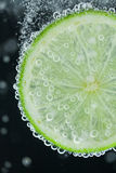 Lime slice falling into water Stock Photography