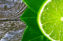Lime slice 2. Slice of lime with leaves on a piece of wood Royalty Free Stock Photo