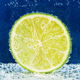 Lime slice in soda water. Lime slice with bubbles in soda water Royalty Free Stock Photo