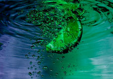 Lime slice in water. Lime slice in swirling, blue and green water Stock Photos
