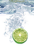 Lime slice in water. Green lime slice under water with a trail of transparent bubbles Royalty Free Stock Image
