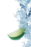 Lime slice in water. Green lime slice under water with a trail of transparent bubbles Royalty Free Stock Photos