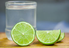 Lime sliced over wooden cutting board with lemonade glass in the background Stock Photography