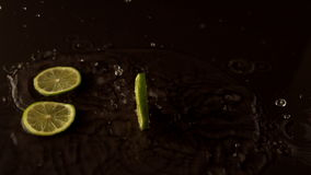 Lime slices dropping on wet black surface stock footage