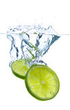 Lime slices falling into the water. Isolated Stock Image