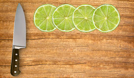 Lime slices and knife on cutting board Stock Photos